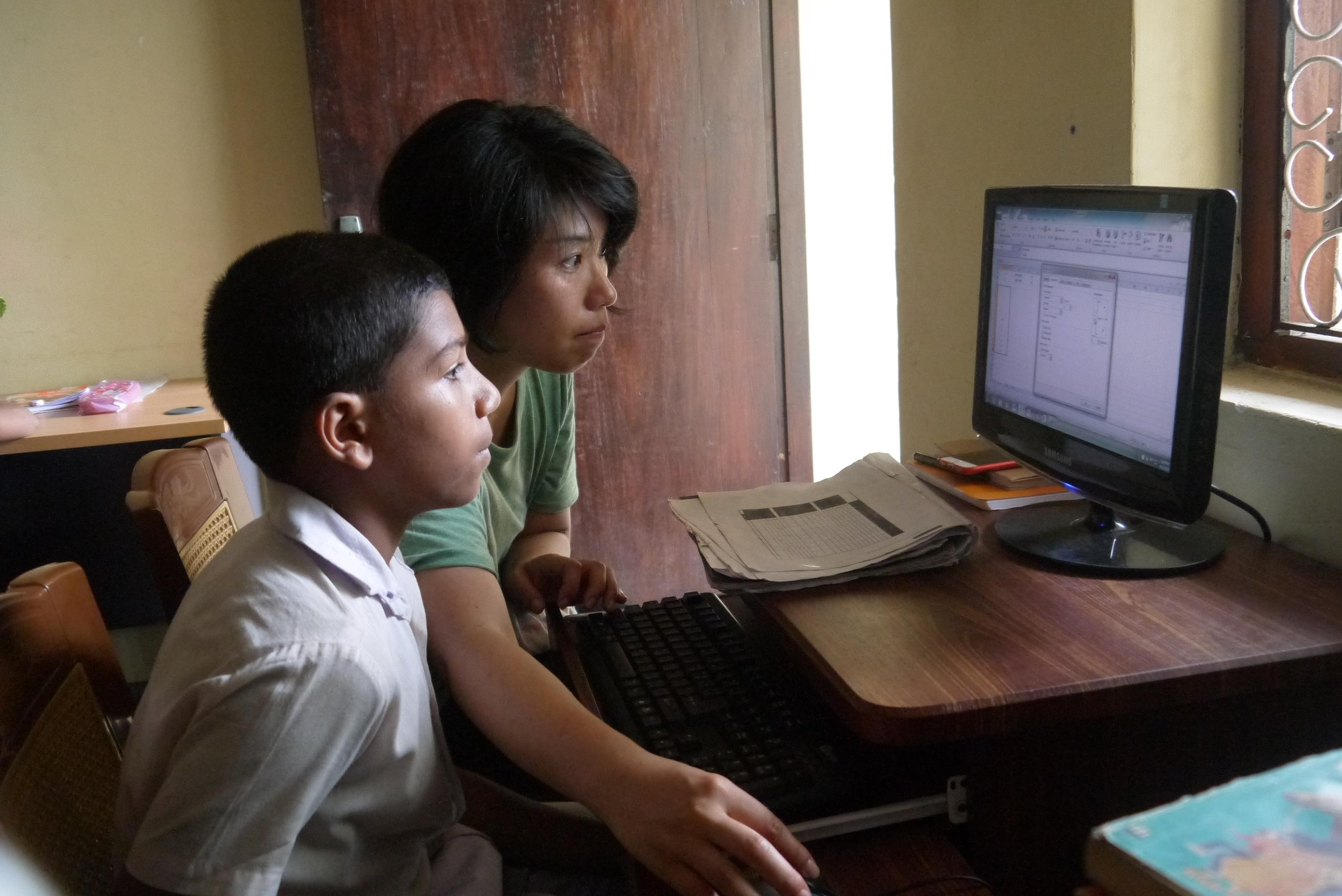 A volunteer helping her student on the computer during her IT teaching work experience in Sri Lanka